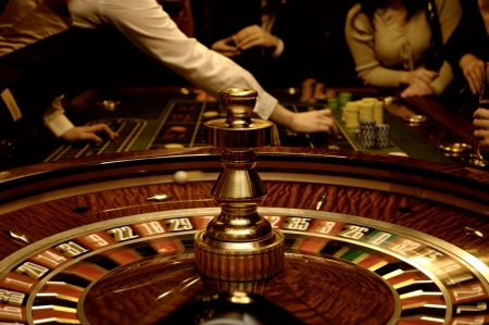 roulette wheel: Gold image of roulette, tabel and players (blurred motion) Stock Photo