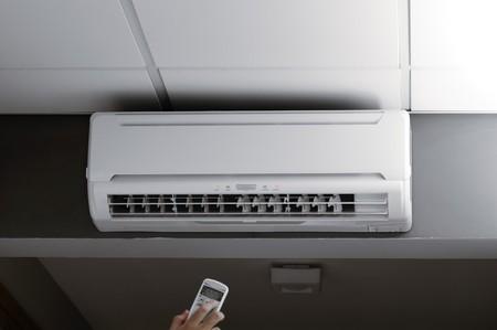 aire acondicionado: Esta fotograf�a representa una mano sosteniendo un controlador remoto de un aire acondicionado  Foto de archivo