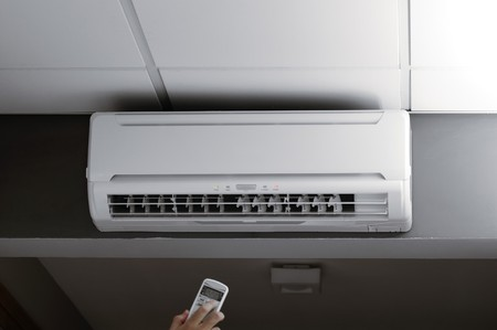 Ventilation: This photograph represents a hand holding a remote controller of an air conditioner