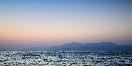 This photograph represent a beautiful sunset on sea and mountain  photo