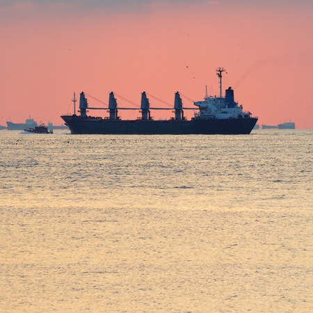 Big cargo ship escorted by small boat to a big sea port with lots of ship in the background, warm sky in background photo