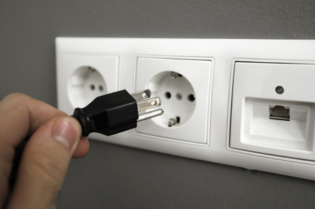 Male hand trying to plugg an american type of plug to an european one. This photograph is a great methaphor for for saving electrical energy worldwide