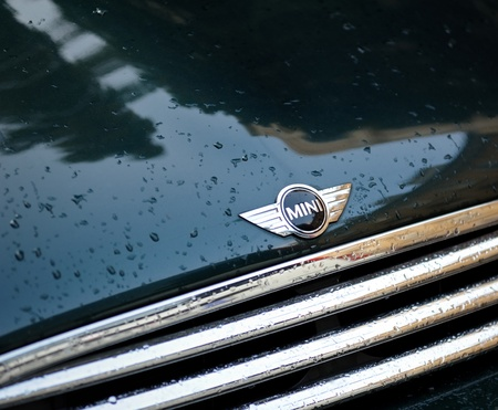 manufactured: Cologne, Germany - 16 June 2011: Photograph of a Mini Cooper, a classical British car manufactured by BMW. Photograph represents the logo, radiator stripes and rain drops.