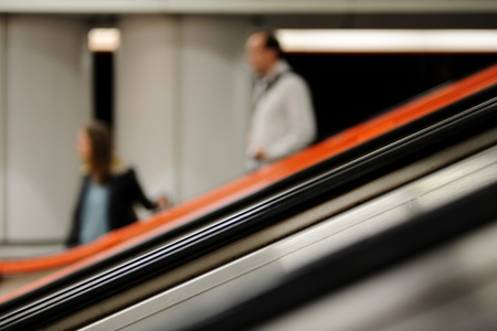 moving down: Unrecognizable women and man moving down on an escalator (blurred motion).