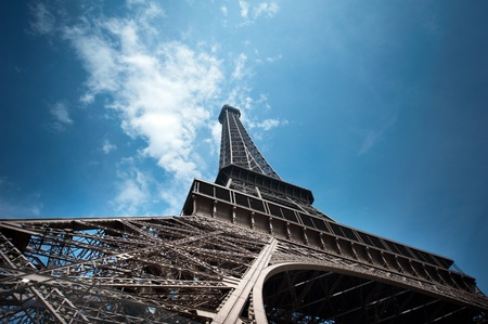 vacance: Eiffel Tower in Paris shot from Champs de Mars against a blue sky shoto from unusual angle. Useful file for your brochure, flyer and website about french culture and architecture. Stock Photo