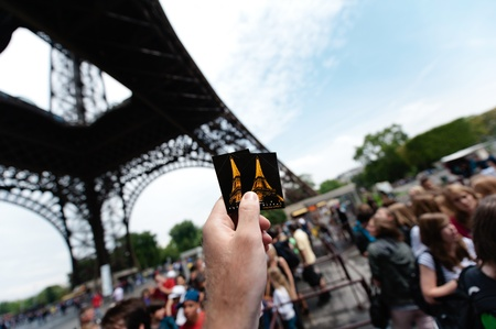 PARIS - JULY 12: Under the monument, a tourist hand is holding two access tickets to Eiffel Tower from Paris, France.The Eiffel tower is the most visited monument of France and probably in the world