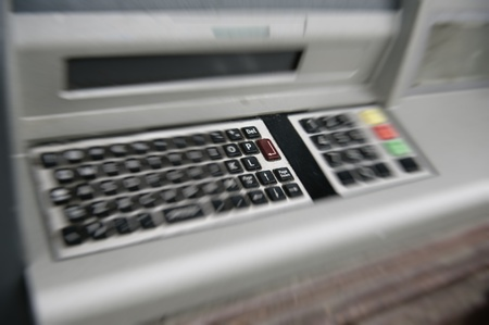 bankomat: ATM (automated teller machine) dirty QWERTY keyboard with focus on Enter button. Stock Photo