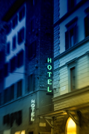 Illuminated hotel signs taken at dusk. Tilt shift lens and intentionally used two gradient glass filter to emphasize the HOTEL letters. Useful file for your site, brochure or flyer about hotel offers. Редакционное