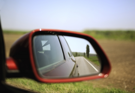 Road and trees reflected in rear-view mirror while driving through agricultural field. Concept file to illustrate an escape to nature from big towns and crowds. Stock Photo - 13647832