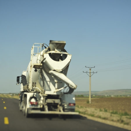 truck concrete mixer: Concrete mixer (cement) truck driving on the freeway. Real tilt-shift lens used to get the special blurr effect. Useful file for your construction article, company brochure and other media needs.