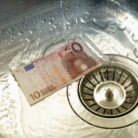 Water rinsing euro note in sink. Tilt shift lens used to accent the note. photo
