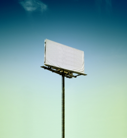 Blank billboard in the middle of nowhere agains blue moody sky. Slightly toned image to concentrate the view on the blank space. photo