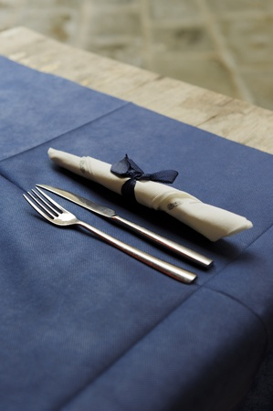 Flatware on blue background with decorative napkin as seen on a  table of a cafe or restaurnat. photo