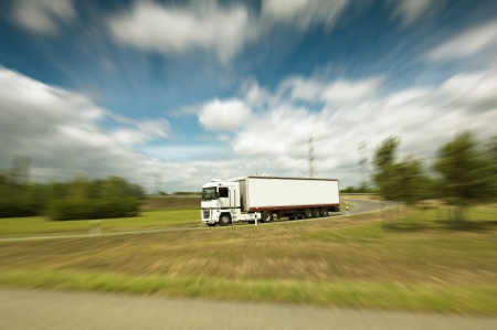 White truck on blurry asphalt under blue sky with clouds