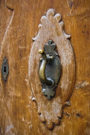 An old metal door-handle knocker on an medieval door photo