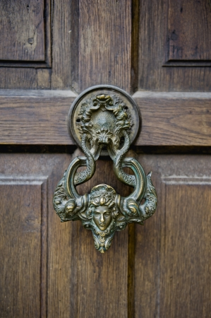 medusa: Old-fashioned grunge door with wooden textures and ancient door knocker with Medusas head. Stock Photo