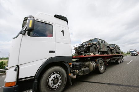 flatbed truck: Frankfurt am Main, Germany - July 4, 2011: Truck carrying lightweight armored vehicles ona a public highway. Editorial
