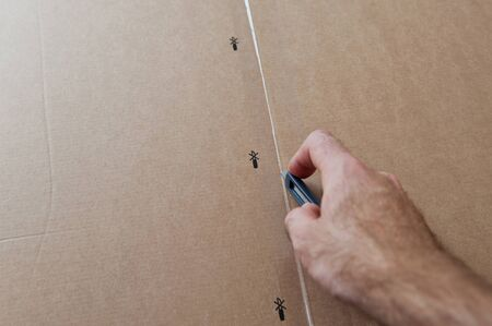 Man cutting a cardboard box with sharp steel box cutter knife to open it. Stock Photo - 17723651