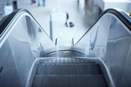 bajando escaleras: Escalera móvil en aeropuerto Tilt-shift lente utilizada para acentuar las escaleras y reparto sublime azul solicitado efecto comercial más