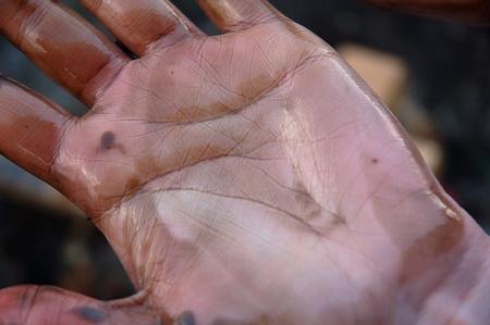 oil spill: La mano della donna sporca di olio dopo la pulizia della spiaggia di una fuoriuscita di petrolio