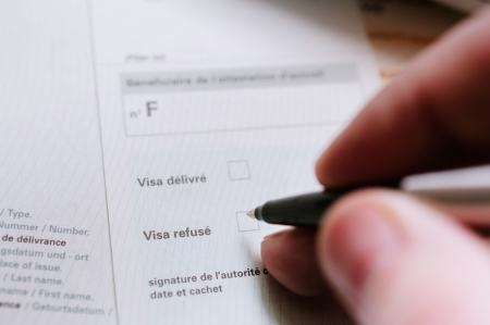 Hand of a consular officer (authority) completing legal form to deny visa issuance. Standard-Bild