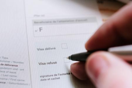 autoridad: La mano de un funcionario consular (autoridad) completando el formulario legal para negar la expedici�n de visados. Foto de archivo
