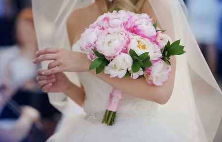 Bride in a white dress touching the ring and holding her wedding peonies bouquet