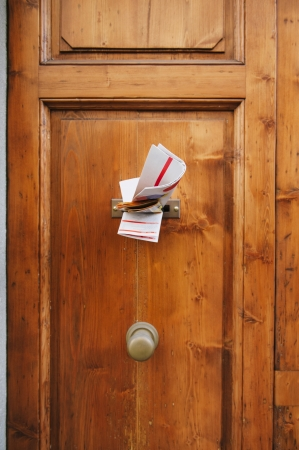 indebt: Multiple magazines in a letterbox of a wooden door. Focus is on the newspaper and magazines. Stock Photo