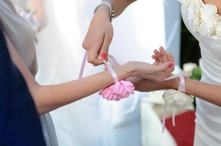 Bridesmaid tying flower on guest hand during  wedding ceremony Standard-Bild