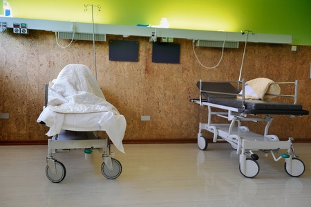 sickroom: Interior of a hospital ward room with two beds. One patient is covered by the bedding sheet other bed is empty.