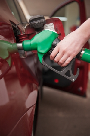 Woman hand refilling up gas tank of the car with green eco fuel on a filling station photo