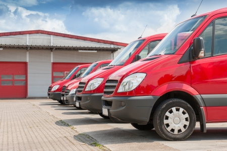 Row of red delivery and service cars in front of a factory and warehouse distribution plant
