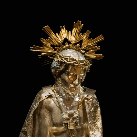 120 year old Jesus gold sculpture at Palma de Mallorca Cathedral on black background. photo