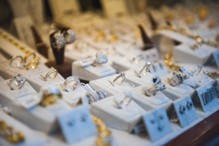 Window display at jewelry shop presenting necklace, rings and earring sets  Tilt-shift lens used to accent the specific objects and to emphasize the attention on it