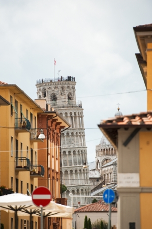 The leaning tower of Pisa in the background of a wonderful italian street in Pisa, Tuscany, Italy photo