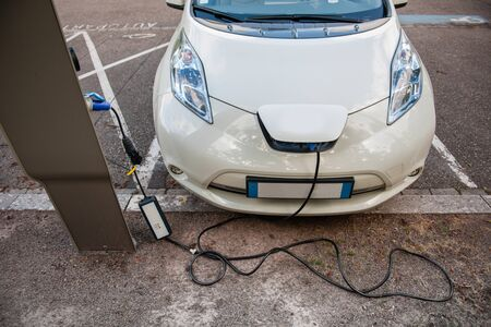 Modern electric car plugged into electricity recharging system station photo