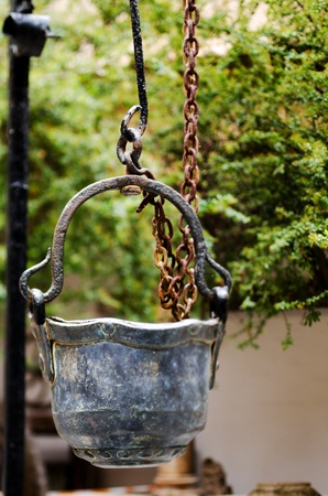 Antique metal bucket used in an old fountain in Obernai, France Stock Photo