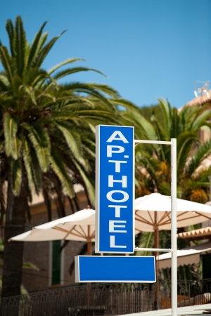 Apart hotel sign on a pillar with umbrellas palm trees behind