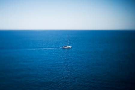 Luxury yacht sailing in tropical calm sea Tilt-shift lens used to accent the boat and to emphasize the attention on it in comparation with the large sea