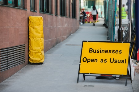 usual: Businesses open as usual sign during re construction of a busy public street in a capital city