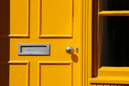 Wooden front door  doorway  in Traditional Georgian architecture freshly painted in yellow color  Standard-Bild