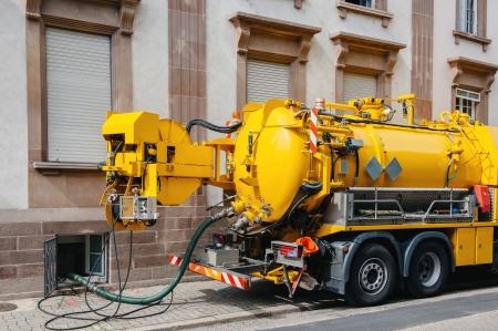 riool: Riolering vrachtwagen op straat werken - opruimen riolering overloopt, schoonmaken pijpleidingen en potentiële problemen verontreiniging door een modern gebouw Stockfoto