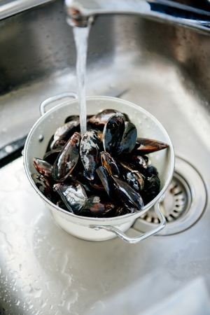 Mussels shells being washed and prepared in kitchen sink