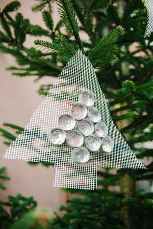 Traditional hand crafted Christmas tree from used candles and mesh on a green tree photo