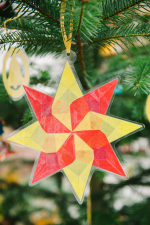 Traditional hand crafted Christmas star from used plastic cover and mesh on a green tree photo