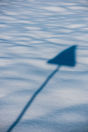 shaddow: Street sign shaddow in form of arrow on a blue fresh snow Stock Photo