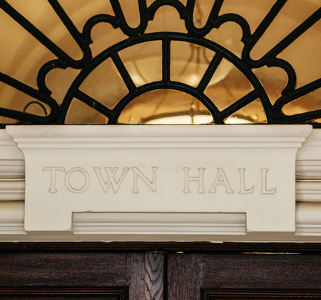 Town Hall sign carved in stone above a wooden door. Фото со стока