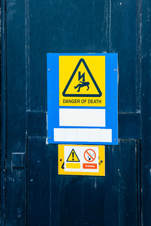 Electrical hazard labels-stickers placed on a fresh blue painted door photo