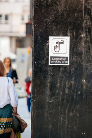urban area: Designated smoking area sign in urban environment