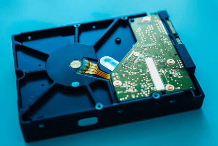 Computer hard drive on blue background (HDD, Winchester). Tilt-shift lens used to accent the center of the hdd and to emphasize the attention its central schemes Stock Photo - 26777066